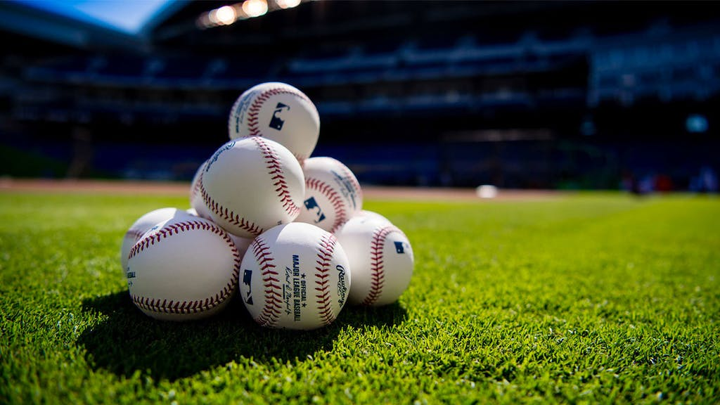 Photo of baseball field with official Major League Baseball balls, background: stadium and green grass